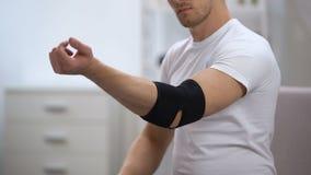 O cotovelo de aplicação masculino novo acolchoou a ortose, tentando mover a mão, ortopedia vídeos de arquivo