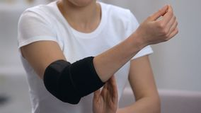 O cotovelo vestindo fêmea acolchoou a ortose no apoio comum, ortopédico doloroso video estoque
