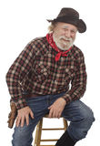O cowboy idoso alegre senta-se em um tamborete Fotografia de Stock Royalty Free