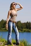 O Cowgirl nas calças de brim está no banco Foto de Stock