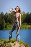 O Cowgirl nas calças de brim está no rio fotos de stock