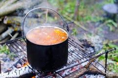 O cozimento da sopa no fogo Imagem de Stock