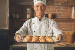 O cozimento do cozinheiro chefe da padaria coze no profissional da cozinha fotografia de stock