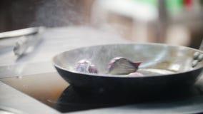 O cozinheiro é contratado em partes quentes de cebolas em uma frigideira, no quadro da mão do ` s do cozinheiro chefe vídeos de arquivo
