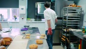 O cozinheiro abre o fogão e põe o pão na tabela video estoque