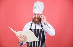 O cozinheiro amador leu receitas do livro Conceito das artes culin?rias r tentativa algo novo Cozinha em minha mente melhore foto de stock