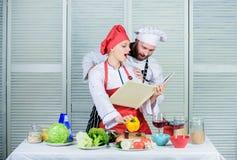 O cozinheiro amador leu receitas do livro r Receitas do livro Livro culinário útil Cozimento do cozinheiro chefe e do homem da mu foto de stock
