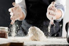 O cozinheiro amassa a massa com farinha na mesa de cozinha imagens de stock royalty free