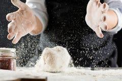 O cozinheiro amassa a massa com farinha na mesa de cozinha imagens de stock
