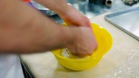 O cozinheiro amassa a massa com mãos filme
