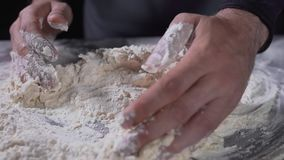 O cozinheiro amassa a massa, a farinha e a água, o pão e a padaria, cozendo na cozinha, cozinhando o alimento, vídeos do alimento filme