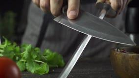 O cozinheiro aponta uma faca no movimento lento da cozinha vídeos de arquivo