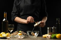O cozinheiro chefe abre e limpa a ostra crua contra um fundo do vinho branco, da alface, dos limões e dos cais fotografia de stock