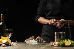 O cozinheiro chefe abre a faca e limpa a ostra crua, no fundo do vinho branco, da alface, dos limões e dos cais Com espaço para foto de stock royalty free
