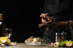 O cozinheiro chefe abre uma ostra em um fundo do vinho branco, da alface, dos limões e dos cais Com espaço para uma inscrição foto de stock