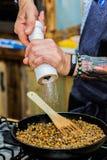 O cozinheiro chefe adiciona ingredientes às refeições foto de stock