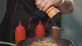 O cozinheiro chefe adiciona temperos no macarronete das fritadas com vegetais e carne em uma frigideira quente filme