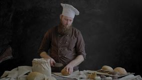 O cozinheiro chefe aponta a faca e o pão da fatia em partes filme