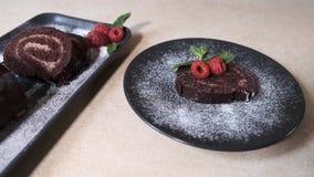 O cozinheiro chefe apresenta e decora o rolo suíço desbastado do chocolate Rolo suíço decorado com framboesas vídeos de arquivo