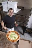 O cozinheiro chefe com fresco remove a pizza Fotografia de Stock Royalty Free