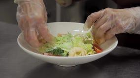 O cozinheiro chefe com luvas adiciona o camarão à salada e aos tomates na placa branca video estoque