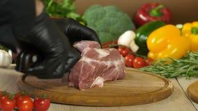 O cozinheiro chefe com luvas pretas toma uma faca e regula uma parte de carne suculenta crua que encontra-se em uma placa de made filme