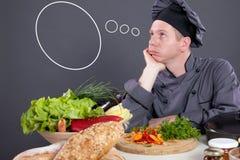O cozinheiro chefe com vazio pensa nuvens, conceito - que a cozinhar hoje? Imagem de Stock