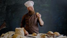 O cozinheiro chefe come uma fatia de pão recentemente preparado para verificar a qualidade video estoque