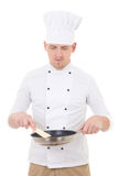 O cozinheiro chefe considerável novo do homem na frigideira guardando uniforme isolou o Imagem de Stock Royalty Free
