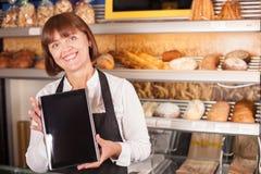 O cozinheiro chefe consideravelmente superior está usando a tecnologia moderna dentro Fotos de Stock Royalty Free