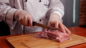 O cozinheiro chefe corta a carne em uma placa de corte video estoque