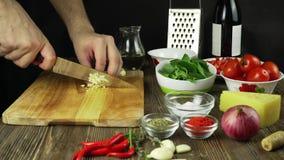 O cozinheiro chefe corta o alho Faca, placa de desbastamento, alho Corte rápido dos vegetais garlic Alho para fritar E vídeos de arquivo