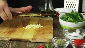 O cozinheiro chefe corta o alho Faca, placa de desbastamento, alho Corte rápido dos vegetais garlic Alho para fritar E video estoque