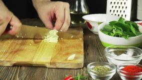 O cozinheiro chefe corta o alho Faca, placa de desbastamento, alho Corte rápido dos vegetais garlic Alho para fritar E filme