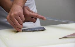 O cozinheiro chefe corta os peixes em partes de sushi Imagens de Stock Royalty Free
