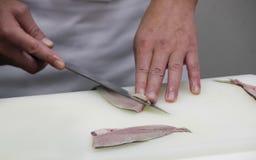 O cozinheiro chefe corta os peixes em partes de sushi Imagens de Stock