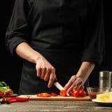 O cozinheiro chefe corta tomates de cereja com vegetais Para cozinhar a pizza, molho de tomate, salada Um conceito delicioso da r imagem de stock