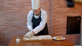 O cozinheiro chefe cortou círculos da emenda rolada da cookie massa crua em uma placa de madeira imagem de stock royalty free