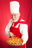 O cozinheiro chefe coze a torta da cereja Fotos de Stock