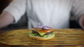 O cozinheiro chefe cozinha o hamburguer e põe os anéis da cebola vermelha nele, fazendo hamburgueres no restaurante do fast food, video estoque