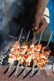 O cozinheiro chefe cozinha no espeto na grade Fotos de Stock Royalty Free