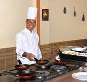 O cozinheiro chefe cozinha a omeleta Imagem de Stock