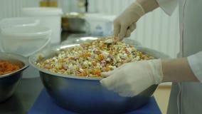 O cozinheiro chefe da mulher prepara uma salada fresca para uma dieta saudável na produção video estoque