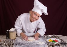 O cozinheiro chefe da pastelaria dá forma à massa de pão do bolinho Imagens de Stock Royalty Free