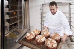 O cozinheiro chefe da pastelaria, leva embora o panettone Imagem de Stock Royalty Free