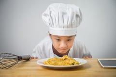 O cozinheiro chefe das crianças está olhando a omeleta no prato Imagens de Stock