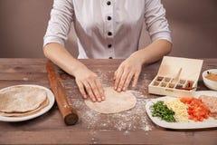 O cozinheiro chefe das mãos esculpe a pastelaria para tacos Imagem de Stock