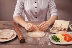 O cozinheiro chefe das mãos esculpe a pastelaria para tacos Foto de Stock