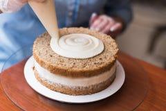 O cozinheiro chefe de pastelaria da menina, faz um bolo de casamento imagens de stock royalty free