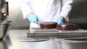 O cozinheiro chefe de pastelaria das mãos prepara um bolo, cobre a crosta de gelo de derramamento do chocolate, trabalhando na pa vídeos de arquivo